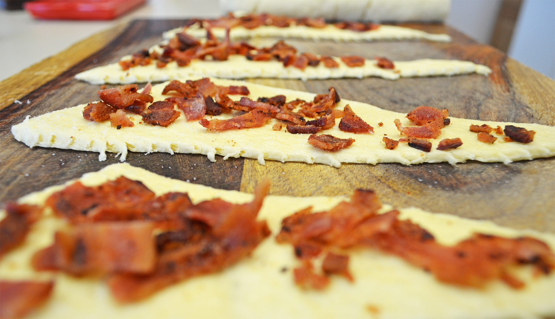 Take ⅛ of your crumbled bacon and sprinkle on each dough triangle ...